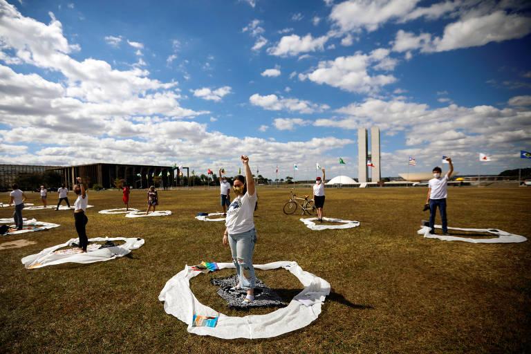 Manifestantes fazem protesto na praça dos Três Poderes. Cada um está dentro de um circulo branco desenhado no chão, com uma certa distância entre um e outro