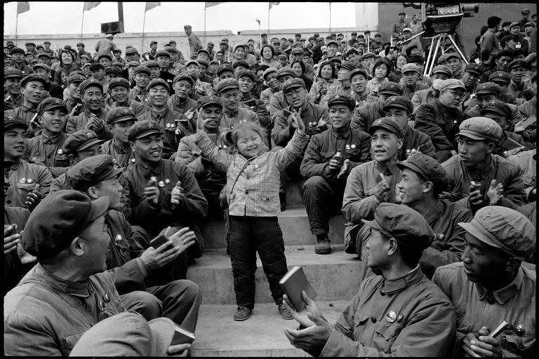 """Criança escolhida como defensora """"do aprendizado e da aplicação do pensamento de Mao"""" faz a """"dança da lealdade"""" para membros do Partido Comunista, em Harbin"""