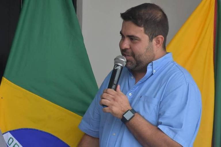 imagem mostra homem de camisa azul falando ao microfone, com bandeira do Brasil ao fundo