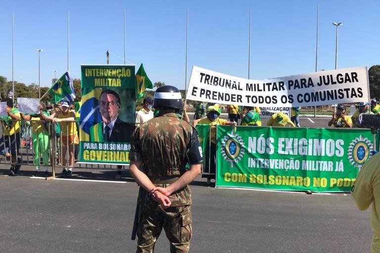 Apoiadores do presidente Jair Bolsonaro seguram cartazes a favor da intervenção militar e com foto do presidente
