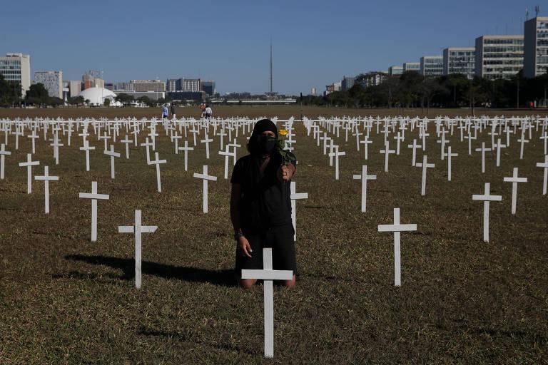 Dezenas de cruzes fincadas no gramado da espanada dos ministérios. Uma manifestante vestida de preto está no meio da imagem