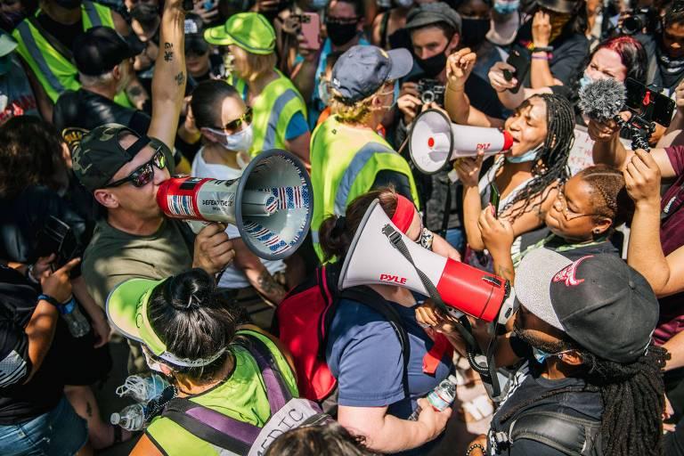 Manifestantes pró-Trump (à esq.) e antirracistas se enfrentam com gritos em megafones em St. Paul, Minnesota