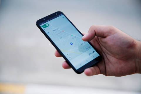 FILE PHOTO: A customer uses Careem application with his smartphone in Mosul, Iraq September 25, 2019. Picture taken September 25, 2019. REUTERS/Abdullah Rashid/File Photo ORG XMIT: FW1