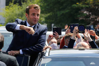 French President Emmanuel Macron enters the car as he leaves after casting his ballot during the second round of French municipal elections, in Le Touquet-Paris-Plage