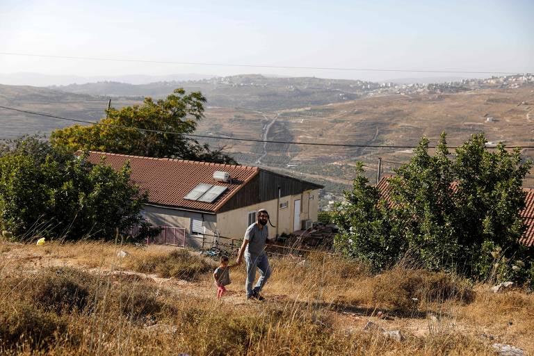 Tzvi Succot, 29, de uma família ultra-ortodoxa, caminha com a filha no assentamento de Yitzhar, ao sul da cidade palestina de Nablus, na Cisjordânia.