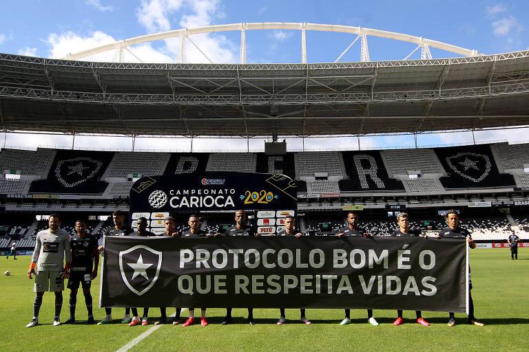 Jogadores do Botafogo exibem faixa de protesto contra o retorno do Estadual do Rio