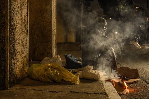 SÃO PAULO / SÃO PAULO / BRASIL - 23 /06/20 - :00h - A cerca de 50 m do hospital de campanha montado no estádio do Pacaembu, vive um morador de rua, no portão 9. Ali, ele coloca seu colchão, faz sua fogueira para esquentar a comida e vive como se nada estivesse acontecendo do lado de dentro do estádio. A existência dele ali, entre mansões da vizinhança e o hospital é uma mostra do tamanho do desastre social que proporciona ao país atingir a marca de mais de  50 mil mortos. Ele vive ali, desde 2012. E está nas ruas desde 2007.   ( Foto: Karime Xavier / Folhapress) . ***EXCLUSIVO***COTIDIANO