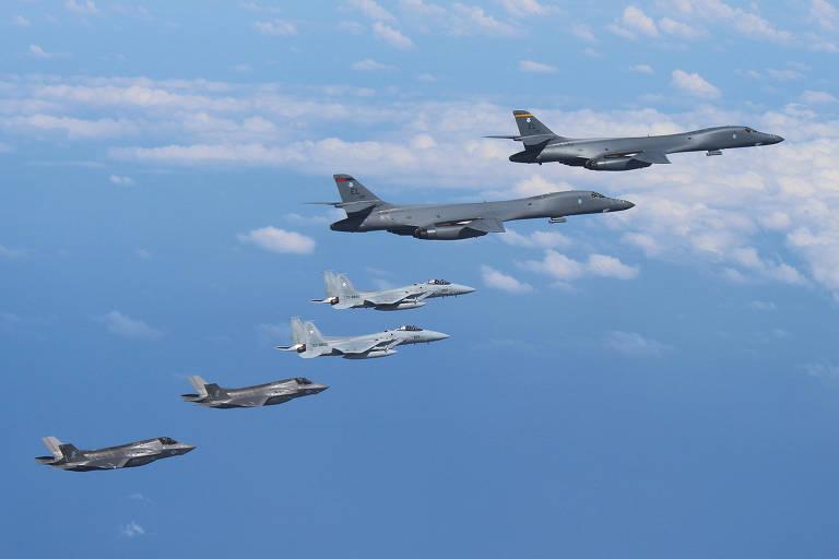 Caças F-15 japoneses (centro) voam com dois bombardeiros B-1B (acima) e dois caças F-35 americanos sobre a região de Kyushu, Japão