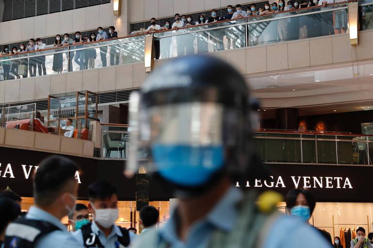 Policiais observam protesto contra a nova lei de segurança em shopping de Hong Kong