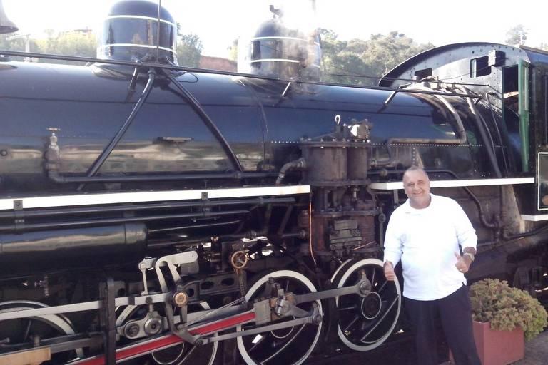 Homem posa em frente a um trem Maria Fumaça, sorri e faz sinal de positivo com as mãos