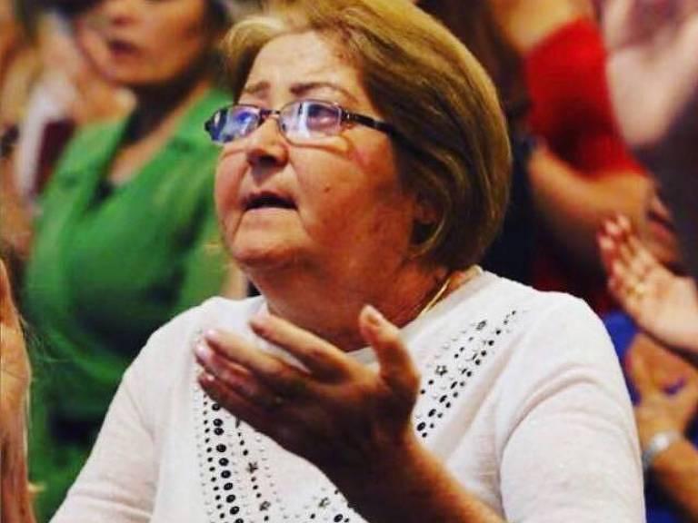 Mulher vestindo branco reza com os braços levantados e a palmas das mãos voltadas para cima.