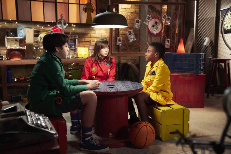 Três crianças sentadas em volta de uma mesa