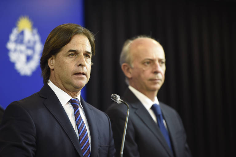 O presidente uruguaio, Luis Lacalle Pou, à esq. durante entrevista coletiva em Montevidéu