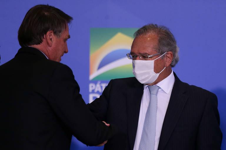 Sem máscara para proteção contra o coronavírus, o presidente Jair Bolsonaro cumprimenta o ministro da Economia, Paulo Guedes, que usa máscara de cor branca, durante solenidade de anúncio da prorrogação do programa de auxílio emergencial, no Palácio do Planalto