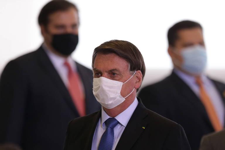 O presidente Jair Bolsonaro. No fundo, deputado Rodrigo Maia (DEM-RJ) e senador Davi Alcolumbre (DEM-AP)