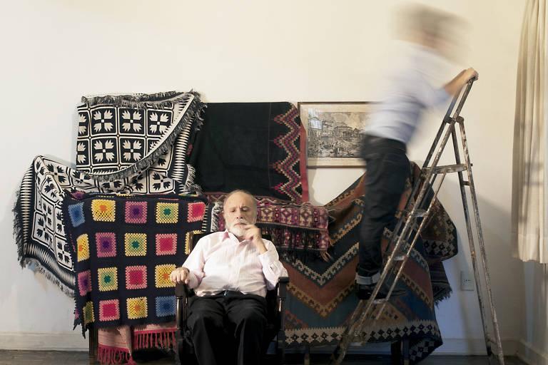 Idoso sentado em cadeira enquanto jovem sobe escada; ao fundo, móveis estão cobertos por cobertores