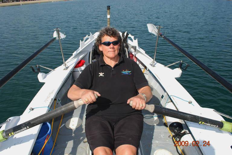 Em um barco branco no mar, Angela Madsen segura um remo com cada mão e os movimenta