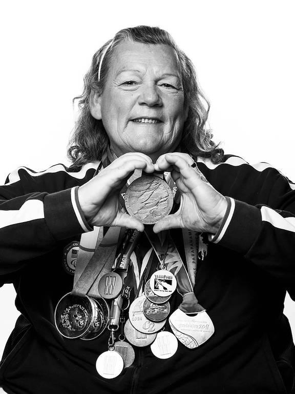 Angela Madsen faz um coração com as mãos e tem suas medalhas penduradas no peito em 2018