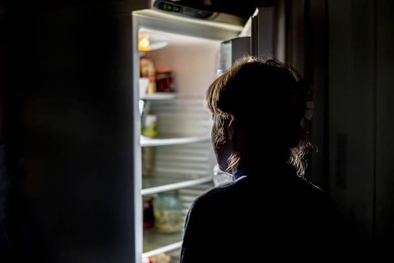 Mulher abrindo a geladeira em um ambiente caseiro escuro