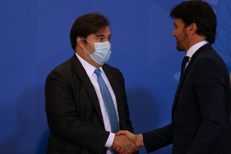 De máscara, Rodrigo Maia cumprimenta Fábio Faria em sua posse no ministério