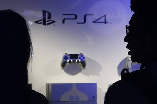 File picture of visitors looking at Sony Corp's PlayStation 4 game consoles and control pads displayed at a booth during the Tokyo Game Show 2014 in Makuhari