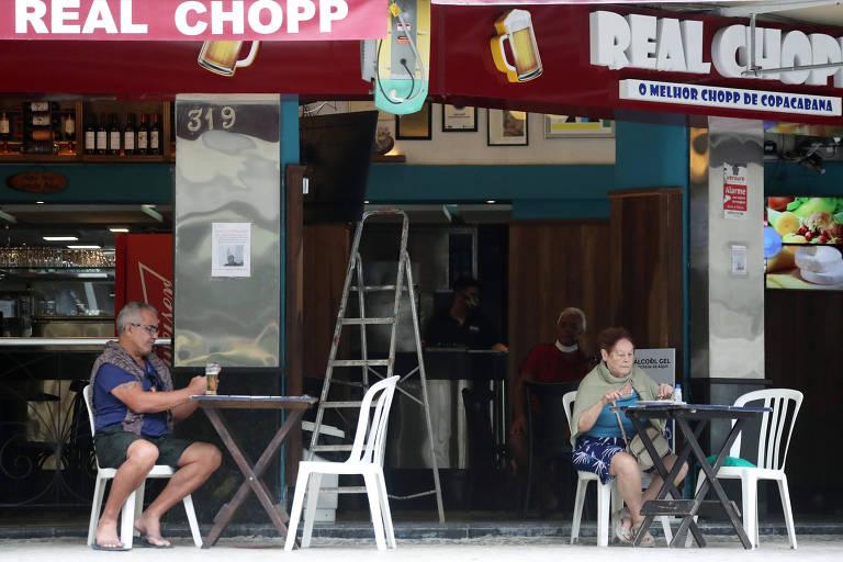 Homem e mulher sentados em mesas separadas do lado de fora de um bar