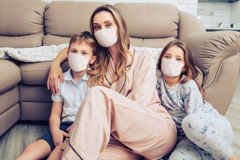 Coronavirus and life concept. Mom is hugging her children sitting on the floor in the room. Home isolation. Family in medical masks at home.