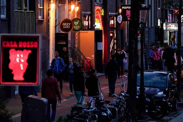 Ao entardecer, pessoas caminham por ruas de paralelepípedos, a maioria está com roupas de frio. Há diversos letreiros de clube de sexo e cafés nas fachada das casas