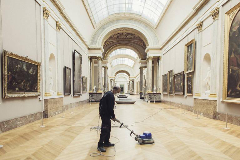Funcionário do Louvre, em Paris, limpa o museu enquanto o espaço ainda está fechado para o público