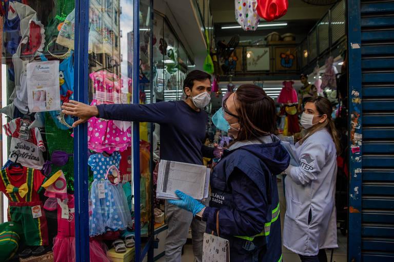 Fiscais da prefeitura e do estado fazem blitz educativa na região da 25 de Março para verificar o uso de máscara; nos condomínios, fiscalização será apenas em caso de denúncia