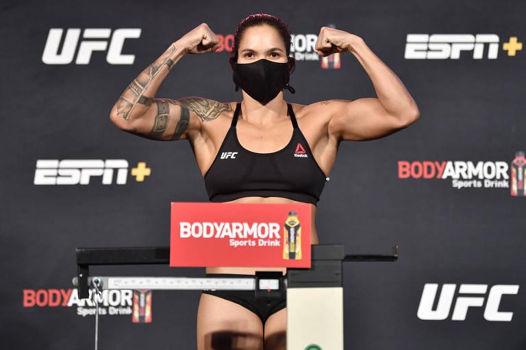 Amanda Nunes, de máscara, ergue os braços e mostra seus bíceps