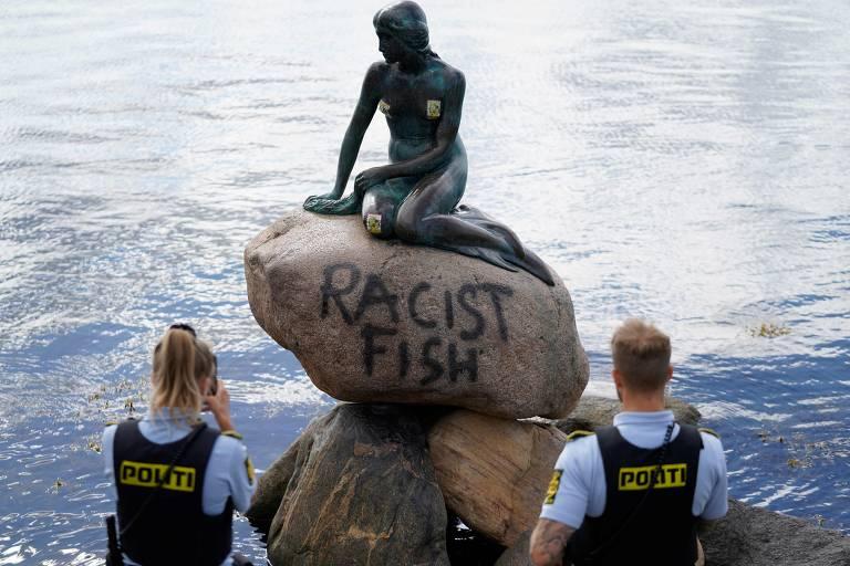 """Policiais dinamarqueses tiram fotos da base da estátua da Pequena Sereia (Den lille Havfrue), em Copenhague, após ela ter recebido uma pichação com o dizer """"Peixe racista"""""""