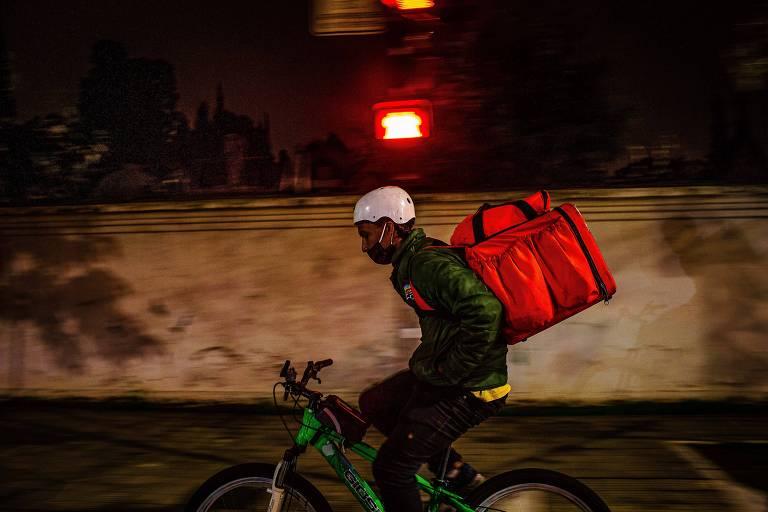 Entregador de comida delivery pedala com as mão no bolso