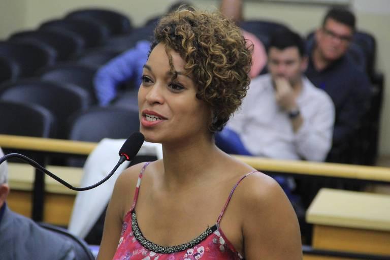 Vereadora falando ao microfone, com público atrás