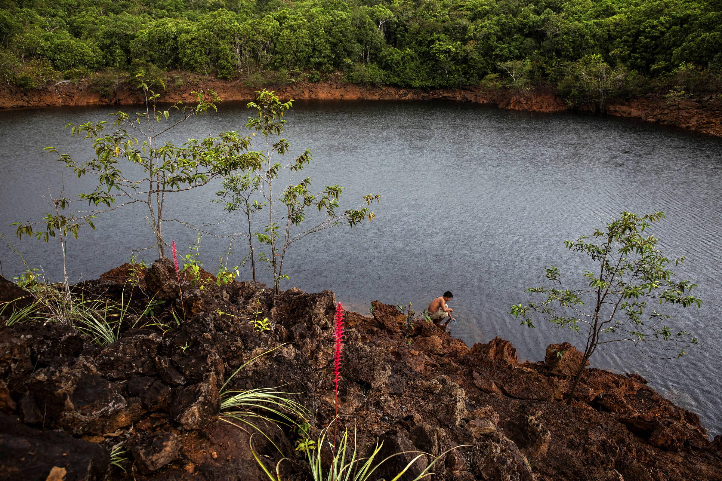 O agente de saúde indígena André Veloso pega água no lago do Dragão