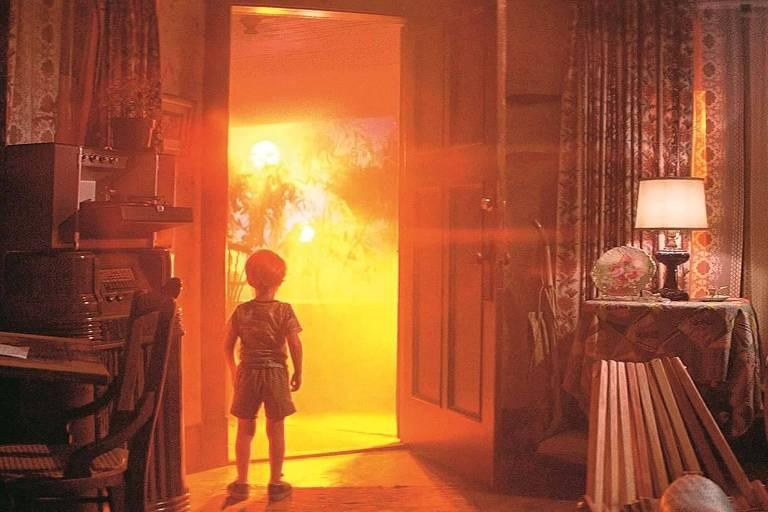 """Cena do filme """"Contatos Imediatos de Terceiro Grau"""", de Steven Spielberg, em que um garoto está parado em frente a uma porta da qual saem luzes muito fortes, como se fossem uma aparição alienígena"""