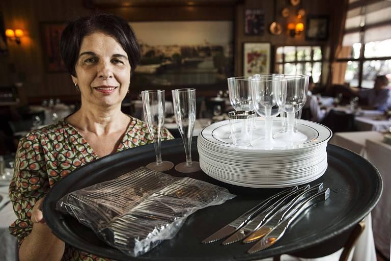 Mulher segura bandeja com pratos talheres e copos de plático