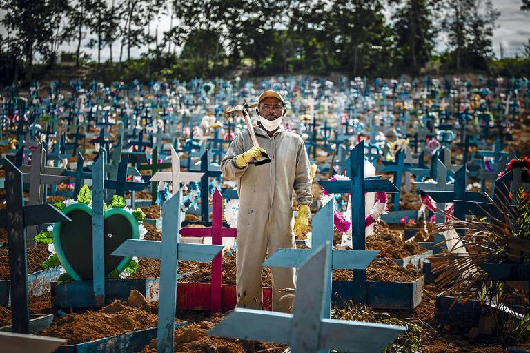 Homem com pá no centro da foto; ao redor, cruzes marcam onde pessoas estão enterradas