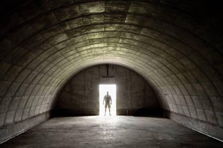 Foto de um bunker em formato de meio cilindro. Um homem aparece na porta do bunker, contra a luz
