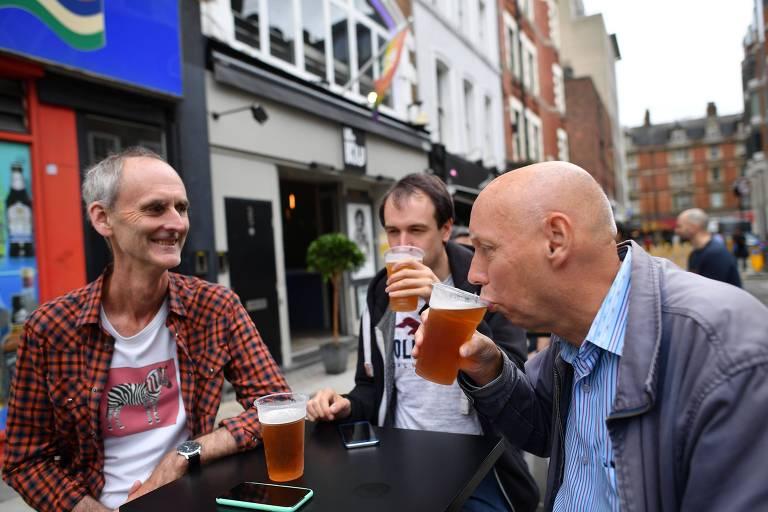 Três homens em uma mesa tomam cerveja em copos de plástico