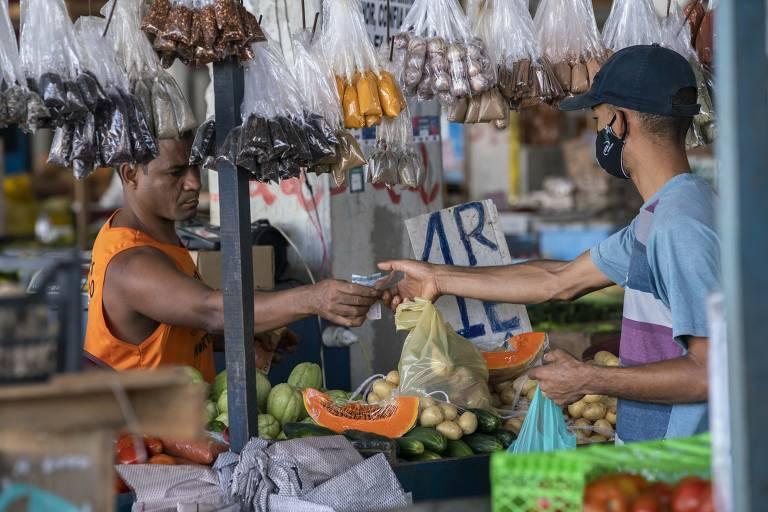 Em barraca de alimentos, o vendedor (sem máscara) entrega troco para cliente, com máscara