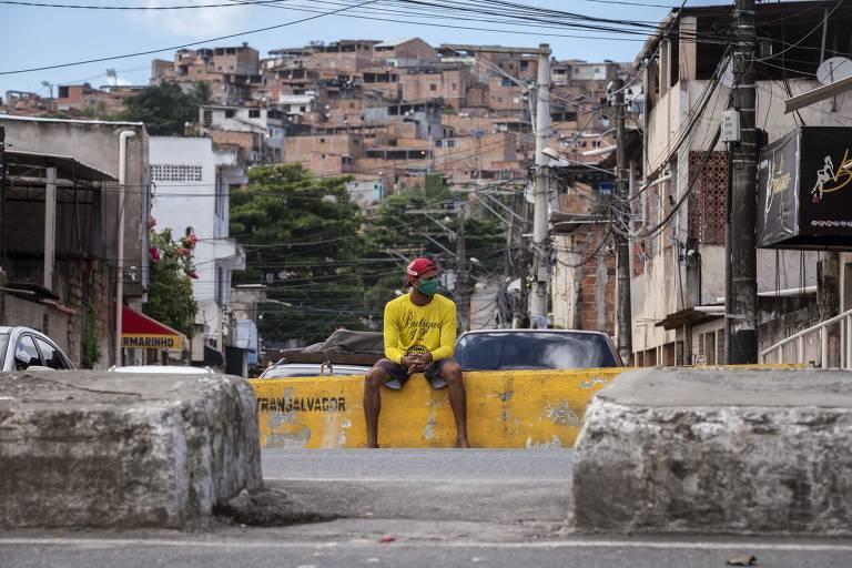 Homem de amarelo com máscara em murinho em praça