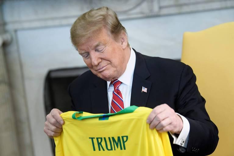 Trump olha cabisbaixo para a camiseta amarela com seu nome
