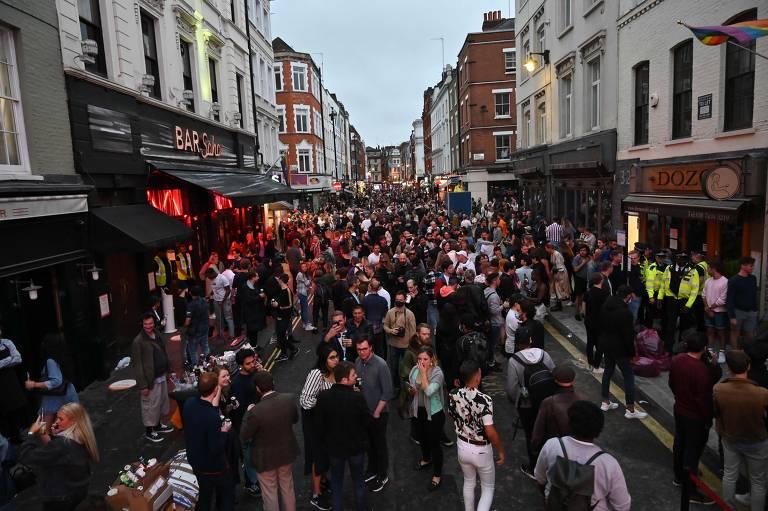 Frequentadores lotam calçadas e a rua em bares do Soho, em Londres, no entardecer deste sábado