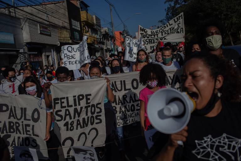 Mulher com camiseta preta e megafone, com outras mulheres com cartazes com nomes, em manifestação