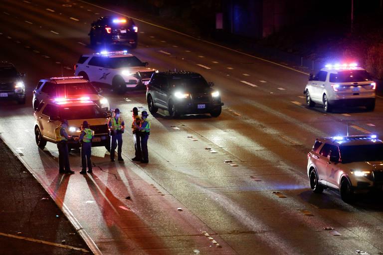 Carros de polícia bloqueiam rodovia enquanto policiais analisam asfalto
