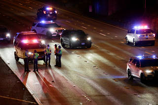 Washington State Patrol investigates the scene where two people in a group of protesters were struck by a car on Interstate 5, in Seattle