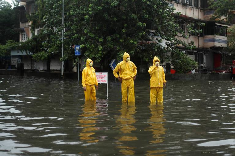 Três pessoas em vestes de proteção amarelas em rua inundada