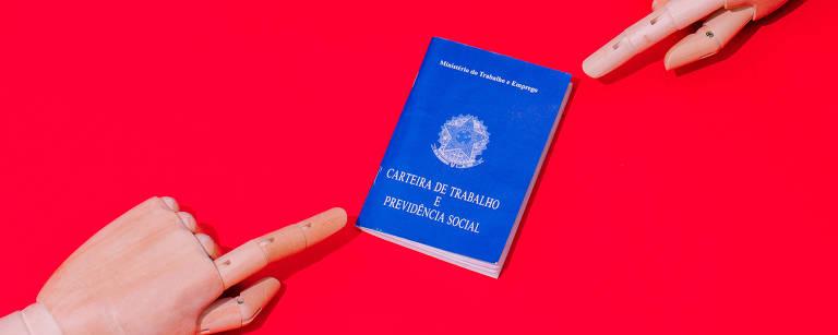 Mãos de boneco apontam para carteira de trabalho (há um fundo vermelho)
