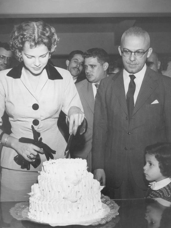 Uma mulher jovem e bonita corta um bolo branco de três andares sob o olhar de um homem mais velho de óculos, terno e gravata e uma criança, numa sala com outros homens de terno e gravata.